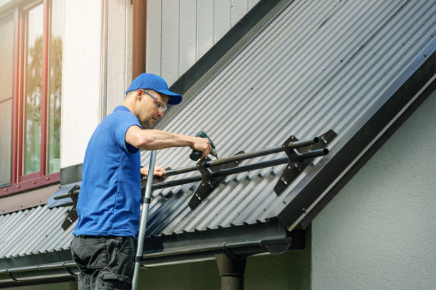 roofer installing snow guard on metal roof stock photo