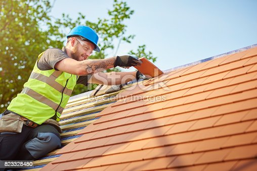 istock roofer nailing clay tiles 823328480