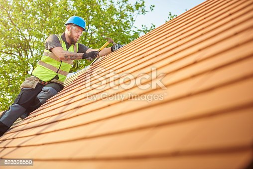 823328086istockphoto roofer nailing clay tiles 823328550