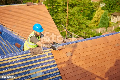 istock roofer nailing clay tiles 823330750