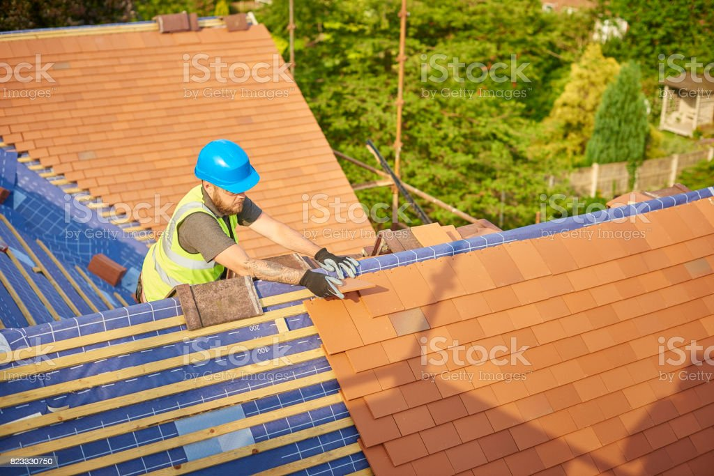 roofer nailing clay tiles stock photo