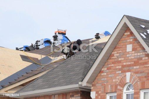Roofer installing new asphalt shingles
