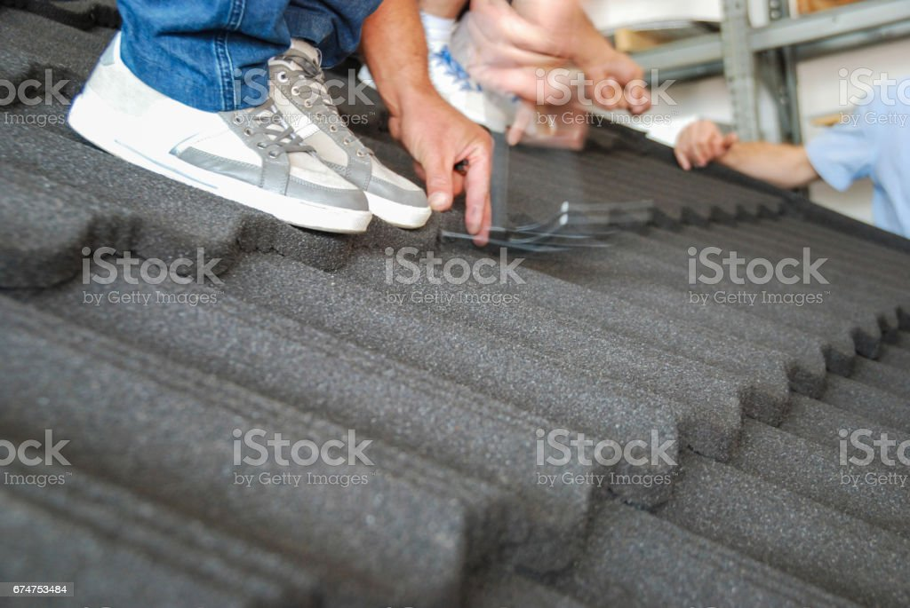 Roofer putting nails in the roof cover stock photo