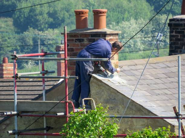 Roofer repairing chimney on slate roof in rural setting. stock photo