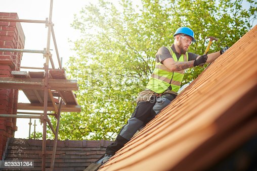 istock roofer replacing the old tiles 823331264