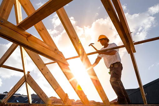 Roofer Worker Builder Working On Roof Structure At Construction Site Stock Photo - Download Image Now
