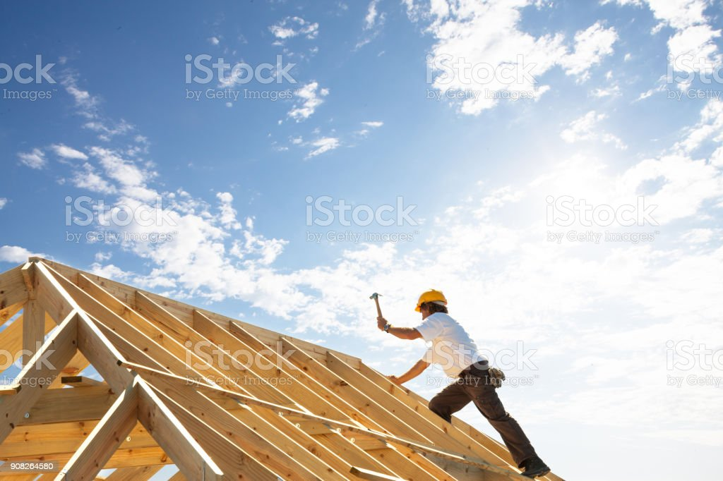 roofer worker builder working on roof structure at construction site стоковое фото
