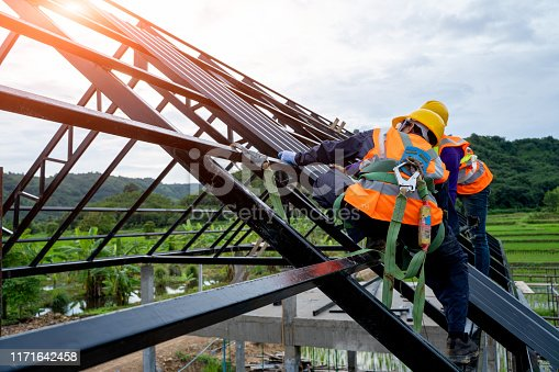 Construction worker wearing safety harness using secondary safety device connecting into 15 mm static rope using as fall restraint shingle on top of the new roof.