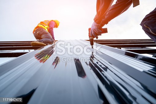 Roofer worker in protective uniform wear and gloves,using air or pneumatic nail gun and installing asphalt shingle on top of the new roof,Concept of residential building under construction.