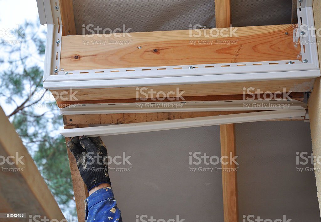 Roofer worker install soffit, eaves, wooden beams. stock photo