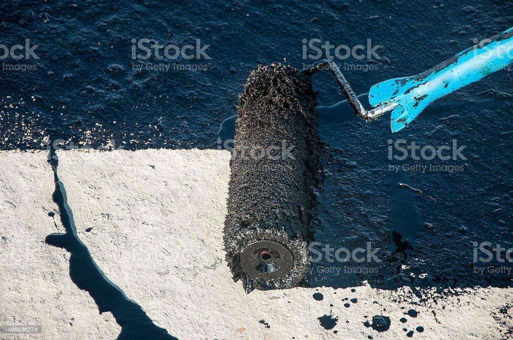 Roofer worker painting black coal tar  bitumen  roller brush,  waterproofing stock photo
