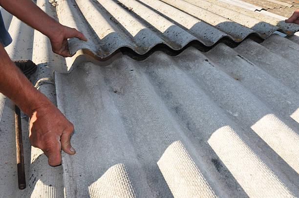 roofers repair dangerous asbestos old roof tiles - dachschräge einrichten stock-fotos und bilder