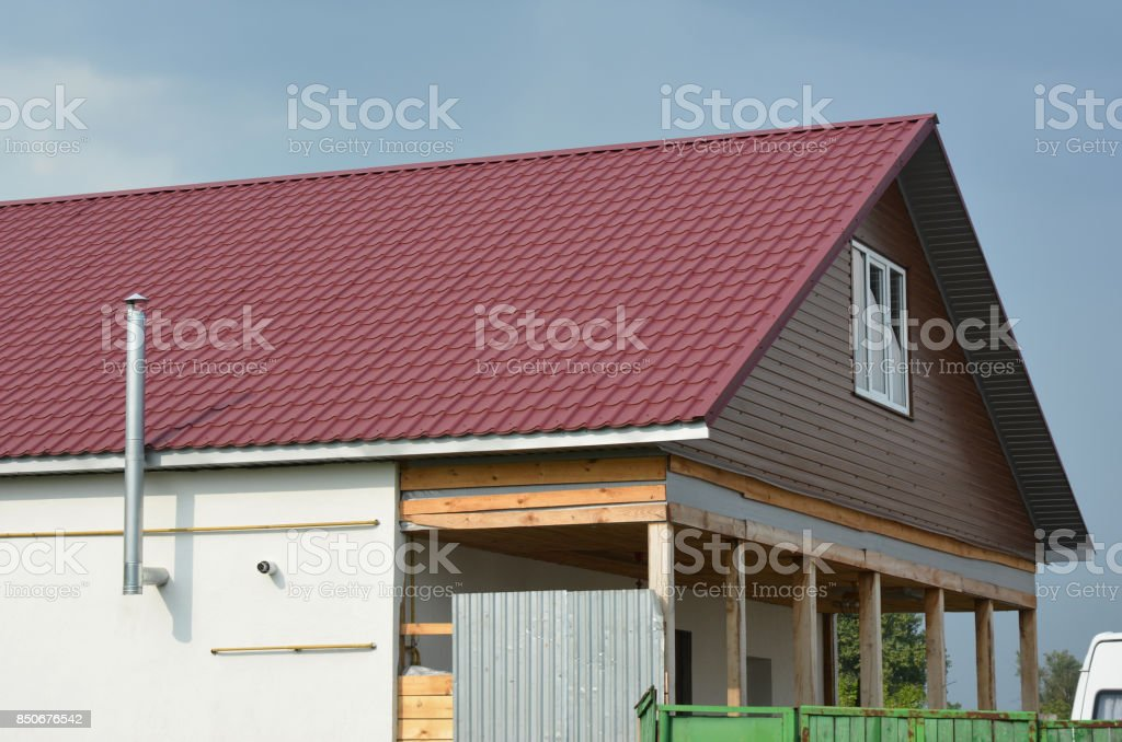Roofing Construction with red metal roof tiles and metal chimney outdoors. stock photo