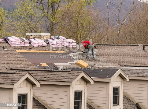 Morgantown, WV - 18 April 2020: Roofing contractors replacing the old shingles on a townhouse roof
