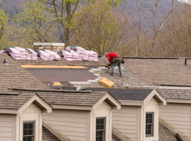 Roofing contractor removing the old shingles from a roof ready for reroofing stock photo