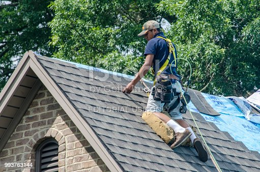 Belmont, North Carolina, USA - June 23, 2018: Roofing contractors replace roofs on residents' homes in Belmont, North Carolina after a hail storm moved through the area on April 15, 2018. Golfball-sized hail was wide-spread and caused much property damage–especially to roofs. Roofing contractors are working seven days a week in temperatures over 90 degrees to meet demand from homeowners. Even at this rate, it could take several years to replace all of the roofs which received damage from the storm.