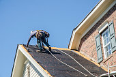 Belmont, North Carolina, USA - June 6, 2018: Roofing contractors replace roofs on residents' homes in Belmont, North Carolina after a hail storm moved through the area on April 15, 2018. Golfball-sized hail was wide-spread and caused much property damage–especially to roofs. Roofing contractors are working seven days a week in temperatures over 90 degrees to meet demand from homeowners. Even at this rate, it could take several years to replace all of the roofs which received damage from the storm.