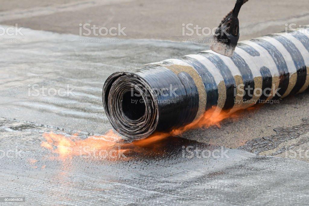 Instalación del material para techos fieltro con calefacción y la fusión roll betún por antorcha de fuego, disparar detalle de primer plano - foto de stock