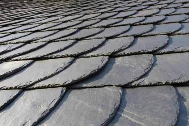 dakpannen: patroon van grijze leisteen op een antieke dak lightend door de zon, Duitsland foto