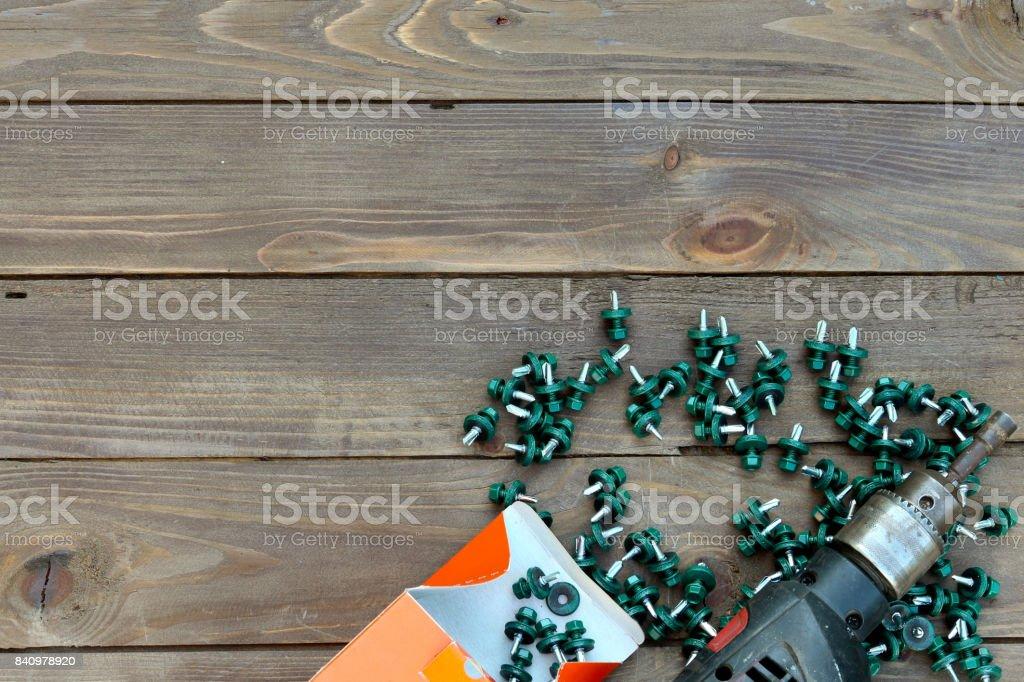 Tornillos para techos y un taladro en una mesa de madera. La vista desde la parte superior. Lugar para hacer publicidad y etiquetas. Techador, trabajo de techos. - foto de stock