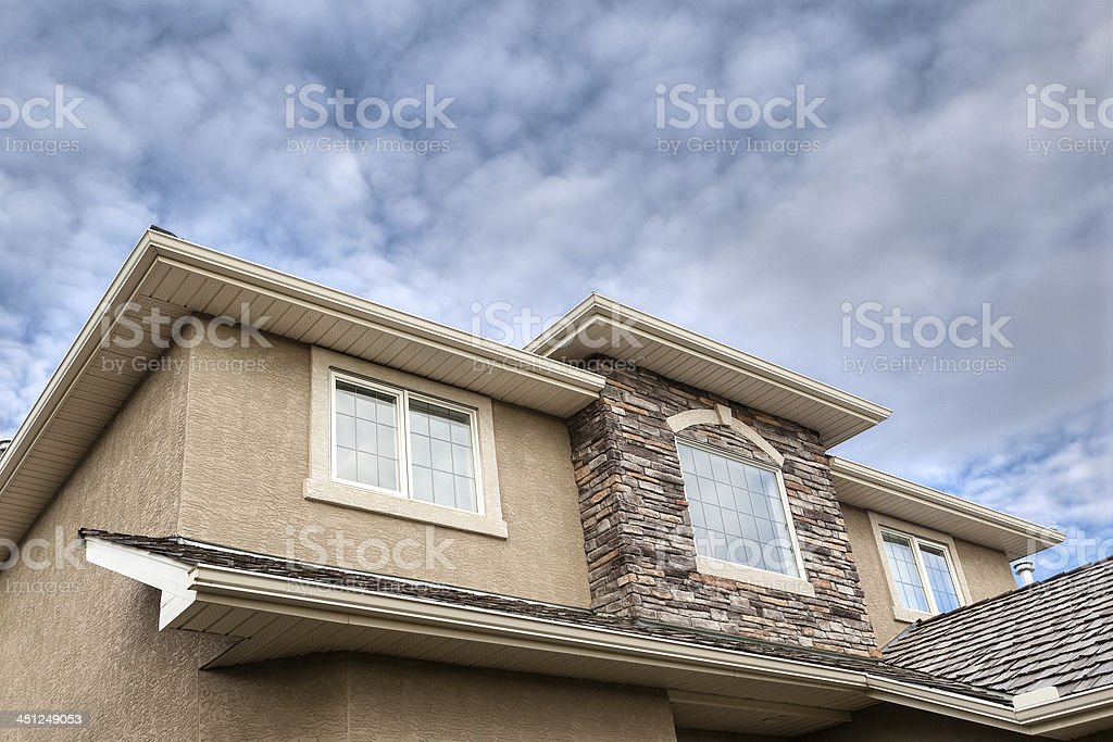 Roofline showing windows, brick stones, gutter, soffit, stucco stock photo