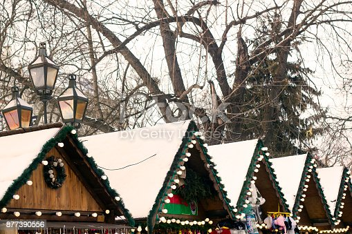 istock Roofs of wooden houses for selling souvenirs at Christmas Fair 877390556