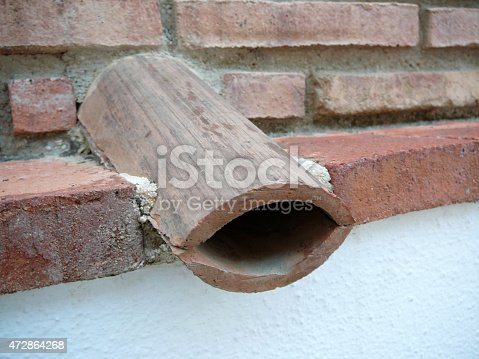 Two roof tiles used to form rainwater drainage in wall
