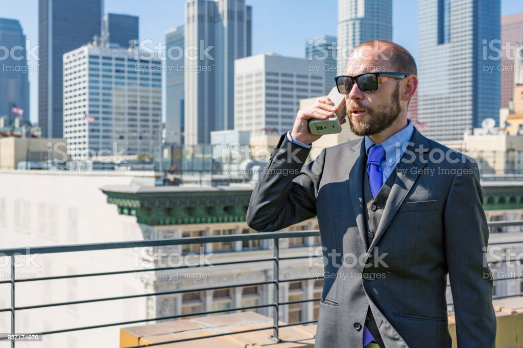 Rooftop Businessman With a Retro Mobile Phone stock photo