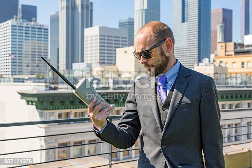 Business man on a rooftop using an old fashioned retro mobile phone
