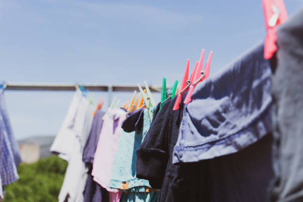 Rooftop drying line full of fresh clean clothes under a blue sky. Selective focus. Detail view. stock photo