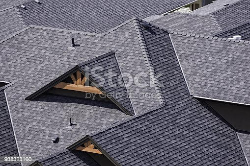 istock Rooftop in a newly constructed subdivision showing asphalt shingles 938323160