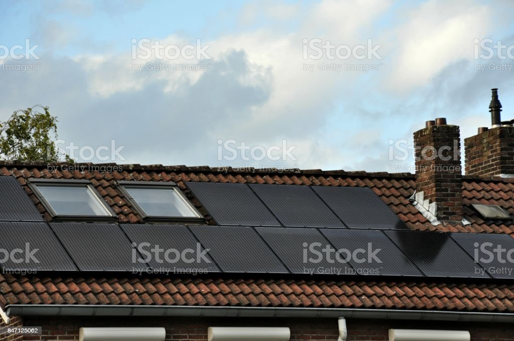 Rooftop of Dutch Home with Solar Panels and Skylights stock photo
