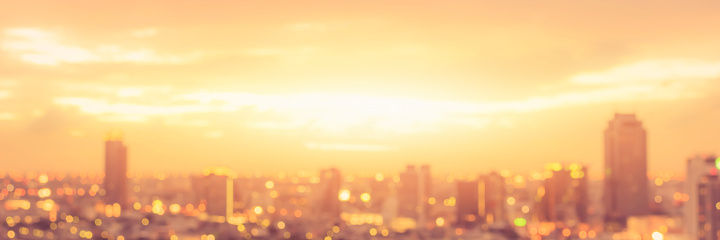 Rooftop party blur city background of blurry sunrise or happy golden hour sunset evening with heatwave, sunmmer sun heat wave, and cityscape buildings skyline backdrop for June Solstice