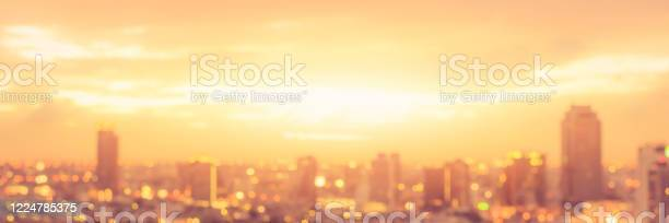 Photo of Rooftop party blur city background of blurry sunrise or happy golden hour sunset evening with heatwave, sunmmer sun heat wave, and cityscape buildings skyline backdrop for June Solstice