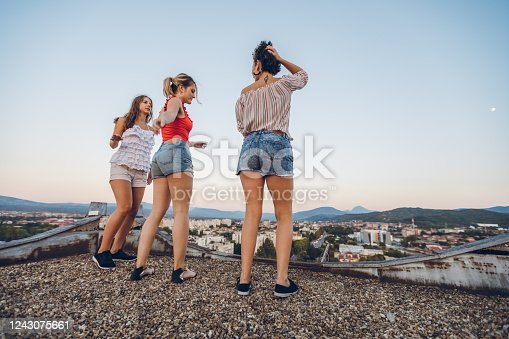 Three female friends dancing on a rooftop.
