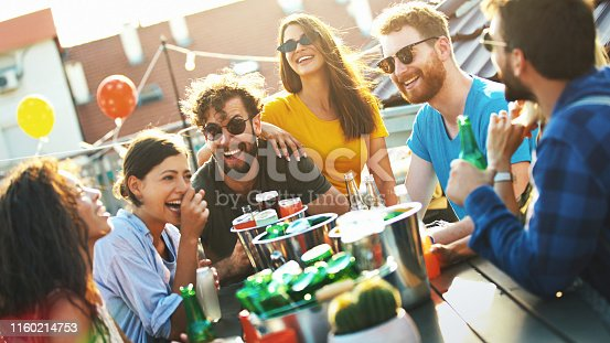 Closeup of group of young adults seated at a big table on a rooftop terrace, having some light drinks, talking and laughing.