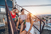 Three, young, happy, women on the rooftop, drinking beer.