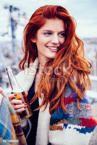 Portrait of red hair young girl drinking beer on the rooftop party.