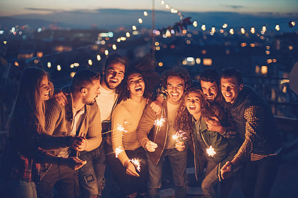 Rooftop party with sparklers at night - foto de stock