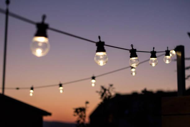 auf dem dach lichterketten am sonnenuntergang - terrassen lichterketten stock-fotos und bilder