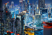 Fantastic rooftop view of city architecture by night. Business bay, Dubai, United Arab Emirates. Nightlife background.
