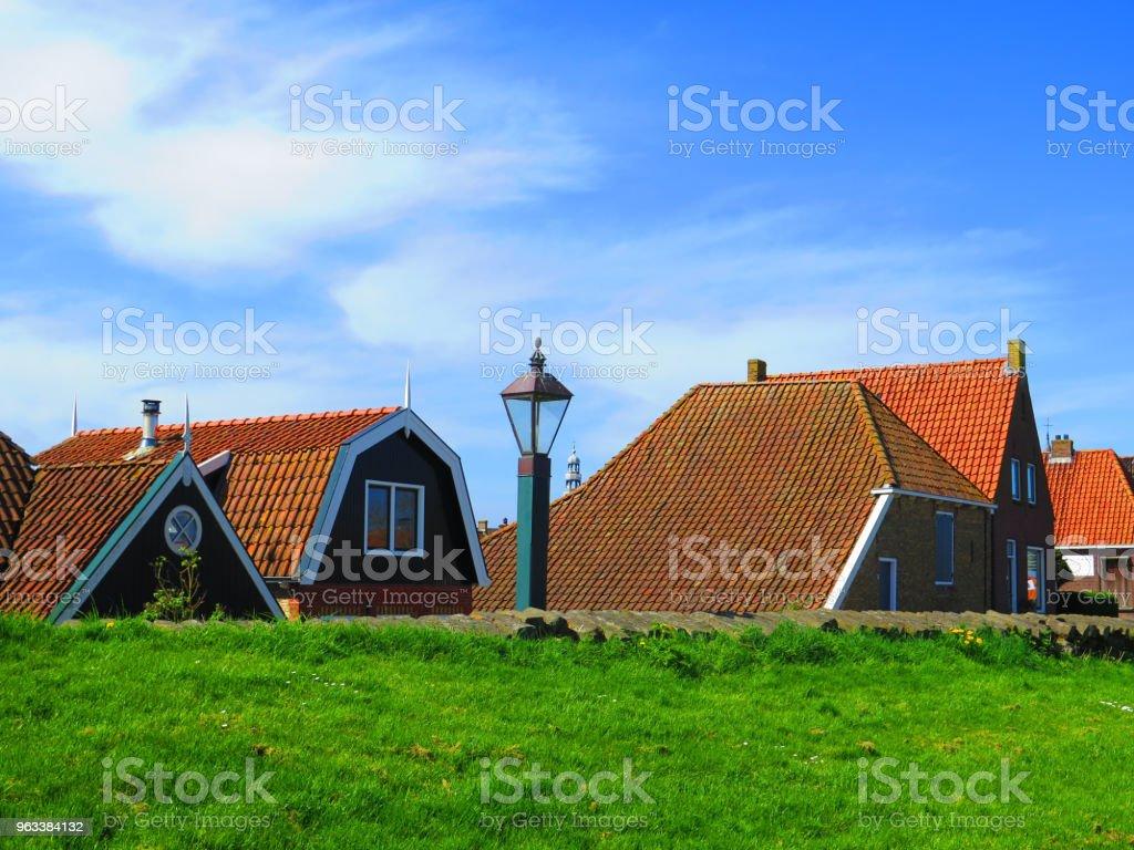 Rooftops visible behind dike in Dutch fishing village - Zbiór zdjęć royalty-free (Bez ludzi)