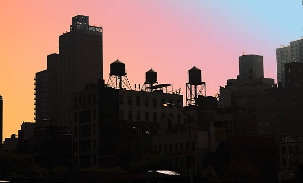 Rooftops with water tanks in silhouette against colorful sky stock photo