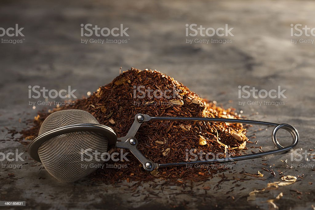 Rooibos Tea and tea-strainer on a metal texture stock photo