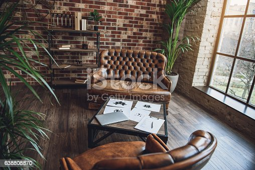 Working of psychologist. Small table between couch and leather chair