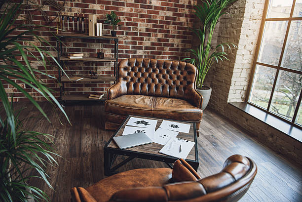 room furnished in loft style - ledersessel braun stock-fotos und bilder