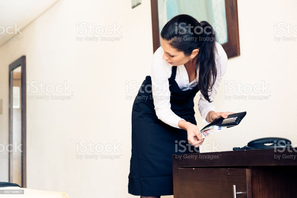 room maid looking through hotel guest's wallet stock photo