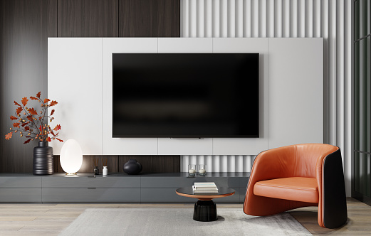 Modern and minimalist living room with 8K TV flat screen wall-mounted. Modern armchair. 3d renderings.