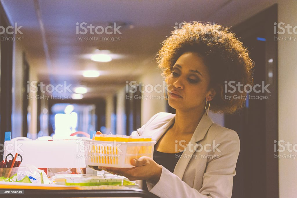 Room service female manager at work Afro amercian woman - room service female manager standing  in hotel corridor next to trolley with toiletries and chcecking products. 2015 Stock Photo