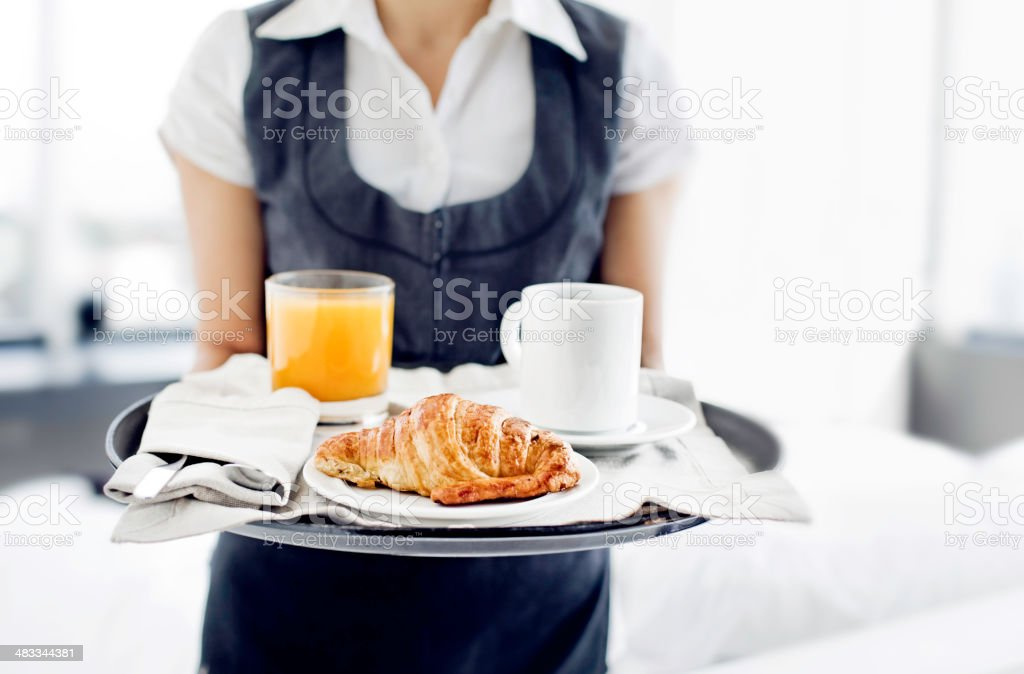 Room service hotel staff carries breakfast tray